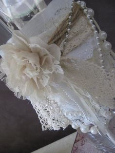 Simple vase decorated with cloth, twine, lace, pearls and a fabric flower