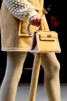 This is a mini shearling Hermes Kelly attached to a matching leather-covered cane. You heard me.