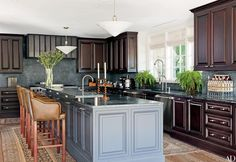 In a Beverly Hills, California, home by designer Waldo Fernandez, vintage milk-glass lights are suspended over the kitchen island, which is painted in Farrow & Ball's Claydon Blue; the dishwasher is by Miele. Painting Oak Cabinets, Beverly Hills Houses, Kitchen Layout, Kitchen Ideas, Kitchen Designs, Kitchen Inspiration, Kitchen Cabinetry, Traditional Kitchen Cabinets, Kitchen Paint