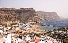 Coastline of Puerto de Mogan in Gran Canaria. Shows rugged cliffs and inhabited area.