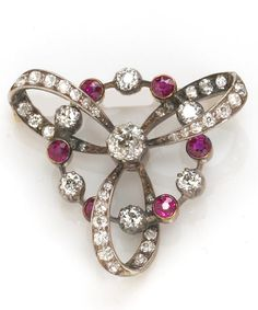 A diamond and ruby brooch  estimated total diamond weight: 1.80 carats; mounted in silver-topped fourteen karat gold; Victorian or Victorian style.