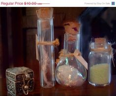 "ON SALE Miniature Potions Bottles by LDelaney on Etsy  These little beakers would look great in a variety of mini settings---laboratories, apothecaries, witches lairs, kitchens, doctor's offices, and cabinets of curiosities! The set includes three small bottles, each filled with varying amounts of three different intriguing and mysterious ingredients. Each jar has a blank label, tied about its neck with a piece of twine. 1"" tall"