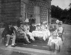 A tea party, in about 1908, outside the huge Palladian mansion of Baron Hill in Anglesey, at which an alert and bearded Edward VII looks at the photographer from among a bouquet of fragrant Edwardian ladies.
