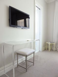 A black flat screen TV hangs above an acrylic table from Plexi-Craft and a stool from Restoration Hardware.
