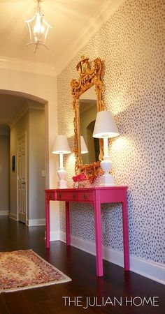 Chic foyer boasts an accent wall painted with a dalmatian print stencil similar to Thibaut Tanzania Wallpaper lined with a hot pink chinoiserie console table and a gold ornate mirror.