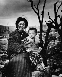 A mother and child sit amid rubble and brunt trees some four months after the atomic bomb was dropped, Hiroshima, Japan, 1945. Photograph by Alfred Eisenstaedt.