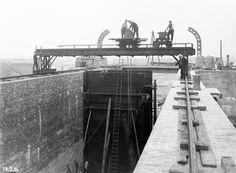 Bau der oberen Schleuse Minden/MLK. Der Verbindungskanal Süd vom Mittellandkanal zur Weser besitzt zwei Schleusen, die nördlichste davon (obere Schleuse) am Kanal.Das Bild (Blick Richtung Süden) zeigt den Einbau des Tores am Unterhaupt mit Hilfe einer schienengebundenen Traverse. Aufnahme aus dem Jahr 1914.