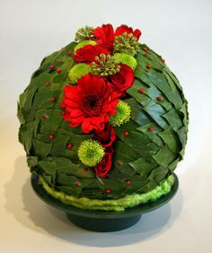With Bay leaves (Laurus nobilis) covered wet foamsphere -.red Gerberas and Roses, lime green spray Chrysanthemums, and Ivy flowers - Chrissie Harten - Design 386