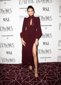 Kendall Jenner wears a burgundy high-neck blouse, slit skirt, and gold lace-up heels