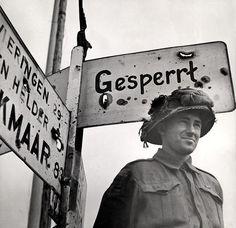 Militair bij Duitse wegwijzer / Liberator near German signpost