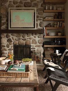 Un salon à la fois rustique et moderne. La cheminée de pierre des champs, la table en bois brut, les chaises en similipeau et le tapis marient une richesse de textures qui font vibrer le décor. À noter, les pommes de pin dans le vase, devant la cheminée, sont une idée de composition originale et simple à réaliser. De plus, le tableau, comme les chaises, contribue à moderniser l'espace, sans le surcharger.