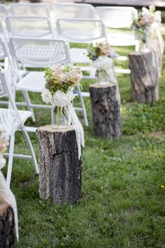 Aisle decor with wooden stumps, mason jars, lace, and mixed flowers  Photographer: Allison Easterling Photography