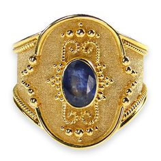 Materials 18k Gold and a Sapphire, Emerald or Tourmaline. Specifics The face is 5/8 inch long and 1/2 inch wide. The ring will be made to your size by the designer for a perfect fit.