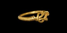 VIKING GOLD KNOT RING 9th-11th century AD  A round-section gold wire hoop with coiled wire to the shoulders, reef knot bezel. 6.99 grams, 24mm overall, 18.43mm internal diameter