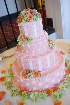 pink polka dots and stripes add fun to this floral topped cake with orange spray roses and green hydrangea
