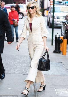 Keeping it casual: The blonde wore a cream boiler suit over a red tank top, with chunky tw...