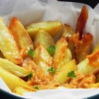 Crispy+potato+wedges+served+with+a+salsa+of+tomatoes,+garlic,+olive+oil,+paprika+and+chilli,+found+on+the+menu+of+almost+any+tapería+around+the+country.