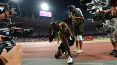 Usain Bolt takes some pictures with a photographer's camera after his Olympic 200m win.