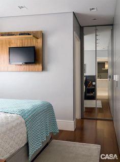 O painel suspenso de freijó (Movelaria Laurel) emoldura a TV e não rouba área de circulação. Manta da Alamanda Home.