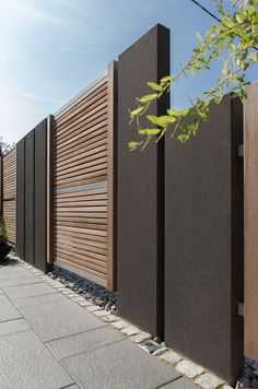 The warm color of the wood with the dark gray of the concrete steles are a modern . The warm color of the wood with the dark gray of the concrete pillars are a modern solution for a privacy screen. Privacy is guaranteed without loss o. House Fence Design, Modern Fence Design, Gate Design, Beton Design, Concrete Design, Boundary Walls, Minimalist Garden, Fence Styles, Backyard Fences