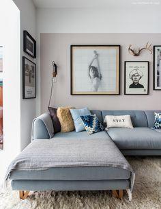 Sala de estar tem parede pintada com tinta rosa claro e sofá azul claro com almofadas estampadas.