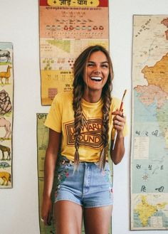 Coachella outfit inspiration to copy. Yellow tee with denim shorts. Long braids hairdo. Fashion trends. Travel outfit. Comfortable. Everyday look. Easy to copy.
