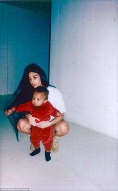 Mother and child: On Wednesday, Kim Kardashian uploaded an adorable photo in which she crouched behind her one-year-old son Saint West and wrapped her arms about him