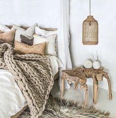 couverture de lit tricoté couleur beige, tapis en fourrure, meuble ne bois brut