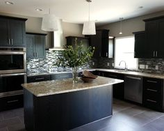 Contemporary open concept kitchen with dark mocha cabinetry, decorative backsplash, and quartz counter tops.