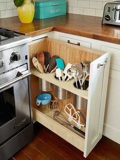 DIY pull out utensil bin right next to the stove, is a clever alternative to the traditional corner cabinet