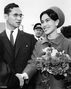 King Bhumibol Adulyadej of Thailand and Queen Sirikit of Thailand, holding a bouquet of flowers, as she shakes hands with an official before boarding an aircraft at London Airport, London, Great Britain, 6 October 1966. The royal couple had been staying in Britain for eleven weeks and were returning home to Bangkok.