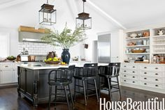 Custom- made cabinets with open shelves are set against a beadboard wall and accented with Rocky Mountain Hardware pulls.   - HouseBeautiful.com