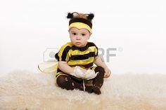 Baby earing bijen kostuum zittend op de vloer, bedrijf bloem, op witte achtergrond Stockfoto - 17457939