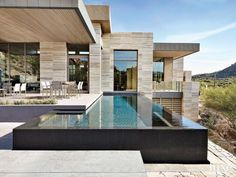 The modernist-style home features a cantilevered roof and multiple levels of stone so that it feels like a continuation of the surrounding boulder-strewn hills. The architect persuaded the owners to include a 15-by-40-foot infinity lap pool, which adds sculptural value.