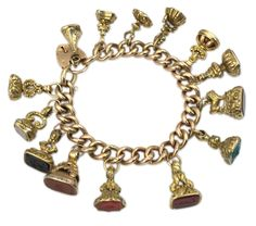 "Hard Stones Charms Gold Bracelet. ""A peculiar charms bracelet composed of an 18kt link chain, suspending fourteen hard stone seals. Circa 1960."" $9,500. [""Peculiar"" was part of the original description, not my commentary.]"