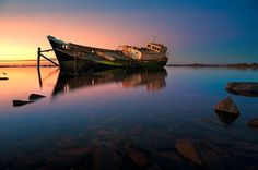 A retired vessel rests in the ship graveyard located in Greenpoint near Bluff, New Zealand.   The Orewa was built in 1898 up in Auckland. It was used as an oyster trawler and a ferry. It's final days were spent in Bluff.