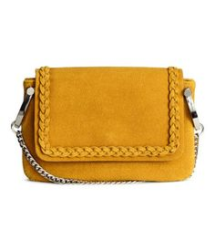 Mustard yellow. Small shoulder bag in imitation leather with surface in  regenerated leather. Flap with decorative braided trim and magnetic fastener, metal