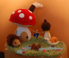 Crochet mushroom house with hedgehog and snail