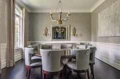 Grey dining room features upper walls clad in gray trellis wallpaper and lower walls clad in wainscoting alongside a chandelier illuminating an expansive round dining table that seats 8 lined with gray velvet dining chairs.