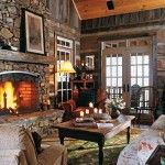A fireplace wall dominates the living room. Composed of local sandstone that was gathered from area creek beds and fitted into place on site, it represents the spirit of the cabin, which is a triumph of reuse, recycling and taking cues from the environment. Susan eschewed new furniture and, instead, outfitted her home using inherited and found pieces
