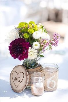 This is the centerpiece I like. Put the table number on the tree slice (in place of the initials). Will also have the mason jar flowers, a smaller mason jar with a candle, and a turquoise votive candle.