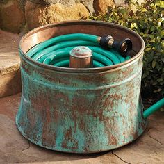 Keep your garden hose hidden inside this old washer tub drum! Great idea!!