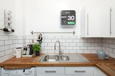 "In the snug kitchen, dark grey grouting adds definition to white Metro tiles; and Muuto's ""Bulky"" tea pot continues the Nordic feel. Habitat sells the ""Flap"" analogue clock."