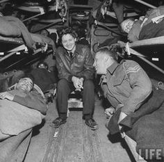 Somewhere over North Africa, an American flight nurse, 2nd Lt. Julia Corinne Riley chats w. injured British soldiers Henry Cowan (L) & George Heathcote (R) while the plane ferries the wounded men from the battlefields to hospitals in the rear; April 1943 ~
