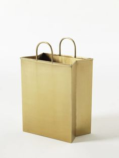 Throw your trash out in style with this unlacquered brass wastebasket in the form of a shopping bag with pinched sides and open handles