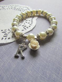 Flower girl, stretchy, initial, heart charm. Lots of rhinestones, sparkles, flower, rose. Choose your color. CHILD sized.    ***********************    Featuring an ivory glass pearl in a stretchy style.  This bracelet features LOTS of rhinestone spacers.  The shine and glamor of this bracelet is MAGICAL.    You may choose you own color scheme.    Measurement and Details:  CHILD sized.    If you stumbled on this bracelet through this listing, please dont forget to visit the rest of our shop…