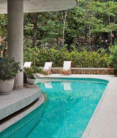 Com forma orgânica, a piscina tem raia que contorna o canto da casa. No fundo, o muro de pedras da região valoriza o paisagismo com plantas tropicais, projeto de Ciça Gorski.