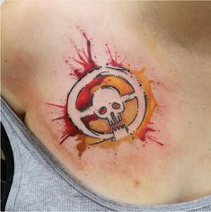 Mad Max: Fury Road Tattoo: A Mad Max: Fury Road Tattoo that is in a shape of a circle but with the center as a skull. The backdrop of the image is a splatter of the colors orange and red.