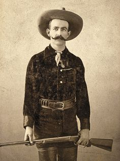 Very likely a Wild West show or vaudeville marksman, the theatrical gent in this circa 1895-1905 cabinet card evokes the latter-day frontier with his Western headgear and thigh-high boots à la Buffalo Bill Cody. He models with a .22-caliber Model 1891 Marlin lever-action repeating rifle having a special order, half-octagon barrel and special order checkered stocking with pistol grip.  – Courtesy Private Collection –