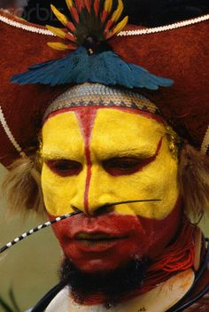 Papua New Guinea | A member of the Huli tribe wears his native dress and yellow face paint. The highlanders of Papua New Guinea usually reserve traditional dress for ceremonial occasions. | © Charles & Josette Lenars